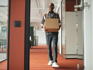 Man walking through office building carrying a box correctly.
