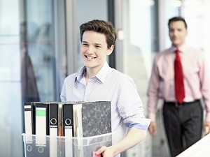Young worker carrying a box filled with binders through an office building.