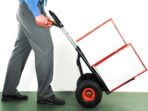 Worker in professional clothing pushing a handcart with two boxes on it.