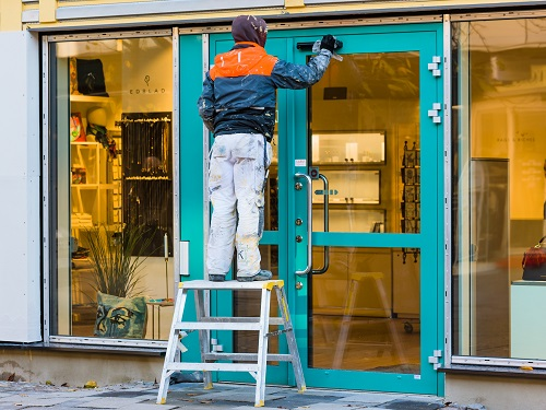 Worker standing on step stool fixing a door on a business.