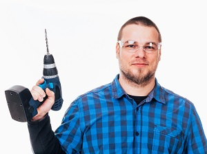 Man Holding Cordless Drill Wearing Safety Glasses