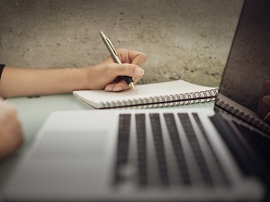 Woman using a pen and notepad to take notes next to an open laptop computer.