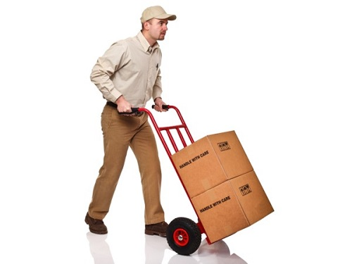 Worker pushing a hand truck with two boxes on it.
