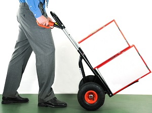 Male office worker pushing a hand truck with two boxes on it.