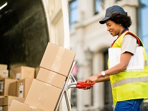 Female delivery driver pushing a hand cart and wearing a safety vest.