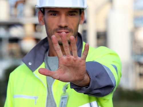 "Construction worker putting his hand out to signal ""stop""."