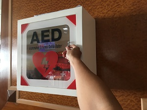 Person reaching for an AED in a wall cabinet.
