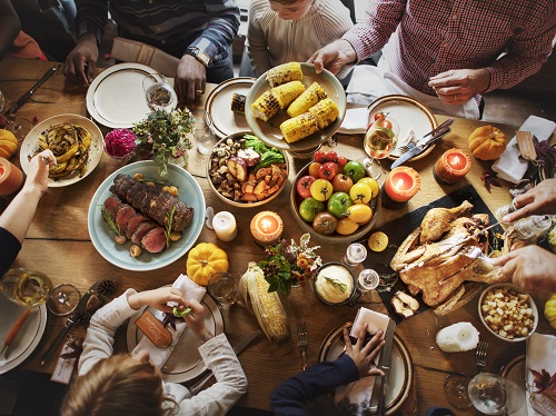 Family around table with a lot of food celebrating Thanksgiving