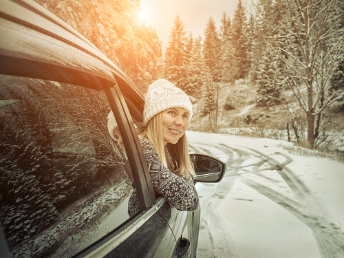 Woman leaning out of car window on snowy road.