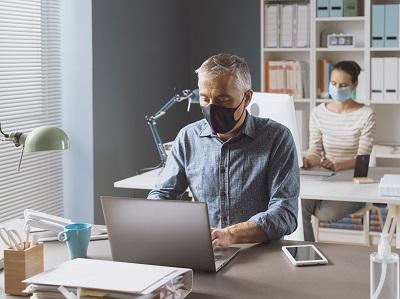 Older worker wearing face mask at work.