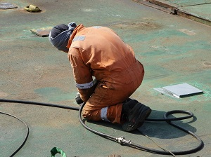 Welder Kneeling Down to Finish Work