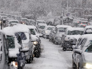 Traffic during a blizzard with lots of snow and cars.