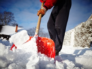Person shoveling snow near their home.