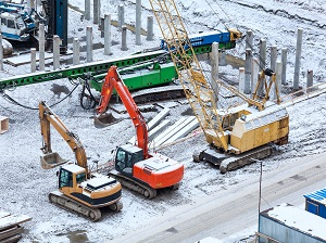 Heavy equipment and excavators on a construction site during winter with visible snow on the ground.