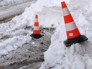 Two orange traffic cones placed on snow mounds near a muddy road.