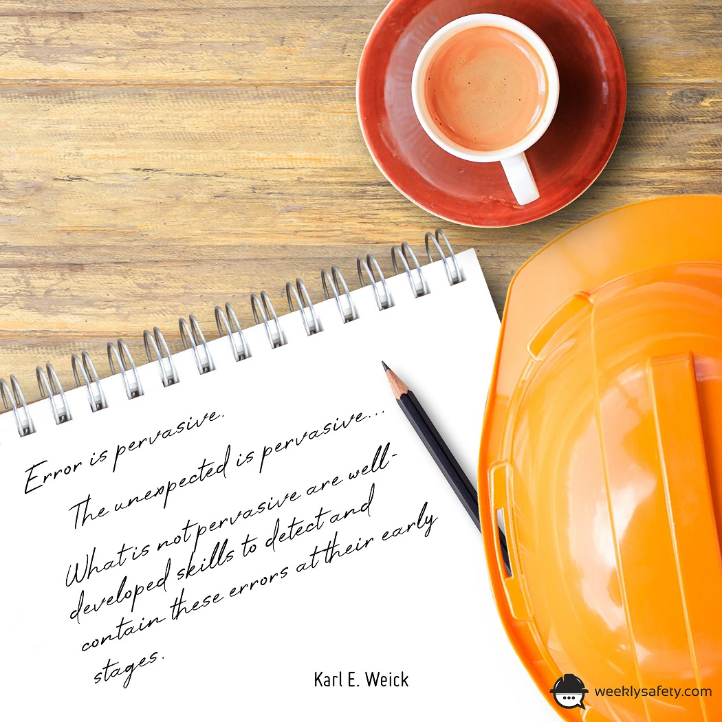On a desk there is a notepad, pencil, orange hardhat and a cup of coffee.