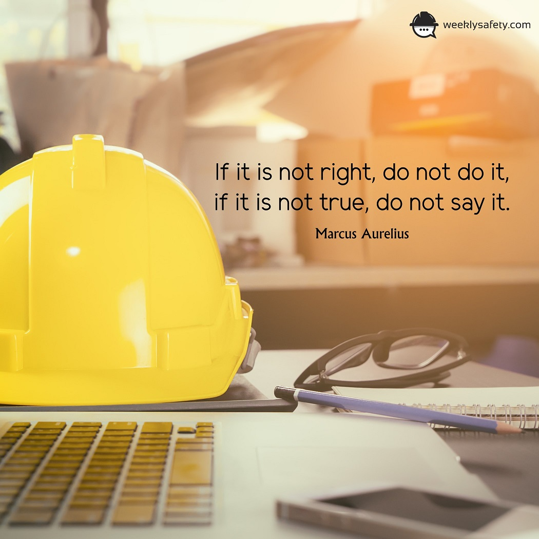 Yellow hardhat and a laptop on a work desk.