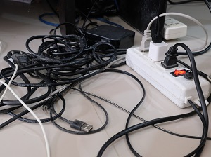 Tangle of electrical cords and surge protector commonly found underneath an office desk.