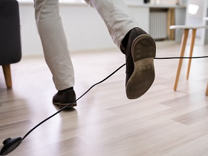 Office worker tripping on an electrical cable laying across the floor.