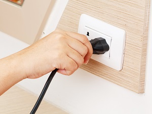 Office worker pushing an electrical plug into a wall socket.