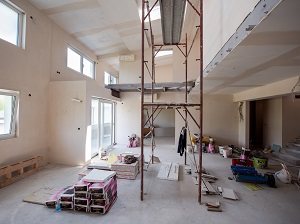 Supported scaffold being used incorrectly in an indoor construction area.
