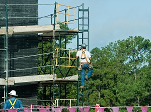 Construction worker climbing onto a scaffold by an attached ladder.