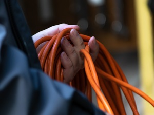 Worker rolling up an orange extension cord.