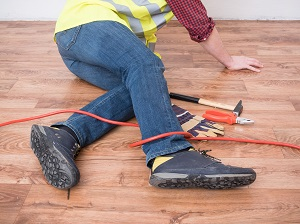 Construction worker has tripped on an extension cord.