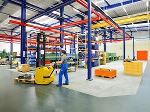 Warehouse with worker using a pallet jack while walking.