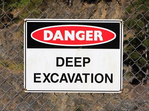 Sign on chain link fence that says Danger, Deep Excavation.