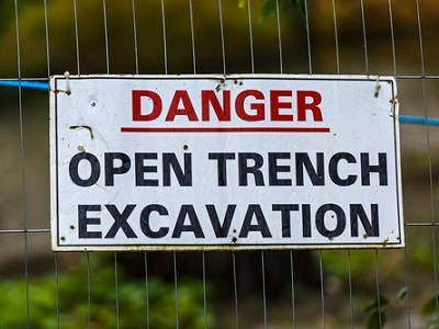 "Sign on a fence that says ""Danger, Open Trench Excavation."""