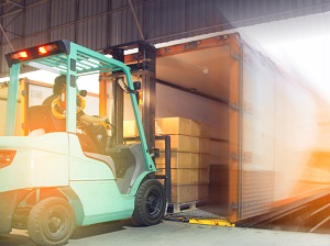 Forklift loading a pallet of boxes onto a truck from a loading dock.