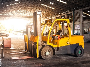 Forklifts parked and waiting to be used in a covered loading area.
