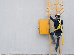 Worker wearing personal fall arrest system starting to climb up a fixed ladder.