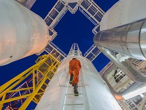 Engineer climbing up a fixed ladder.
