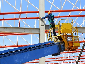Worker on an aerial lift dangerously standing on the side rails.