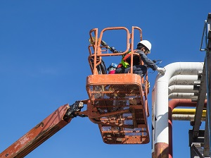 Worker on an aerial lift performing pipe maintenance.
