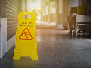 Foldable, yellow, caution wet floor sign visible in a facility.