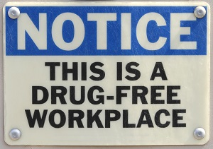 """Sign bolted to the wall that reads, """"Notice, this is a drug-free workplace."""""""