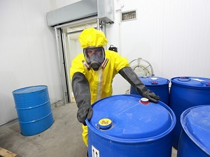 Worker wearing PPE while handling large canisters of hazardous materials.