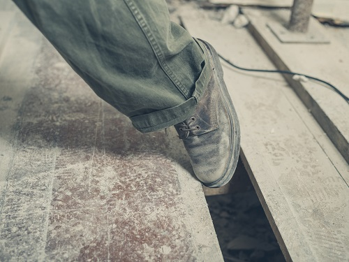 Construction worker's boot getting tripped into a floor hole on construction site.