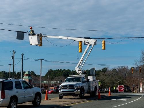 Worker in a bucket truck fixing a traffic light.