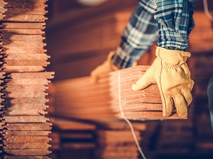 While wearing work gloves, a worker is removing a long bundle of wood from a pile.