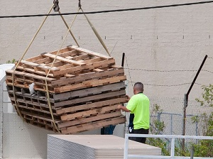 Construction workers moving pallets with a crane demonstrating a caught-in risk.