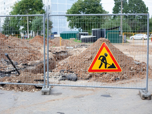 Outdoor construction site where trenching is occurring surrounded by a chain link fence and a hazard warning sign.