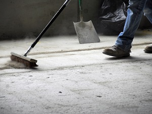 Worker sweeping up a dirty floor.