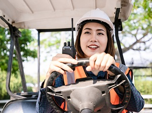 Smiling woman wearing PPE while driving a golf cart.