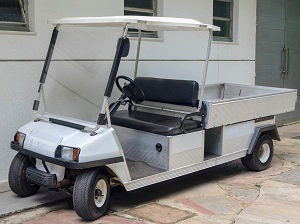 A parked two-seat golf cart with a truck bed for transporting materials.