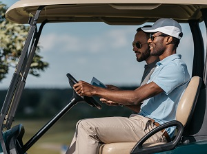 Two men in a two-seat golf cart.