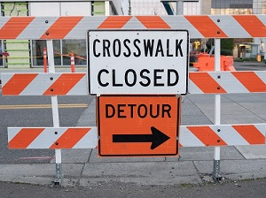 Orange and white street barricade with two signs that say Detour and Crosswalk Closed.